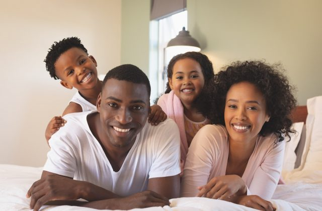 front-view-of-happy-african-american-family-lying-on-bed-and-looking-at-camera-in-a-comfortable-home.jpg